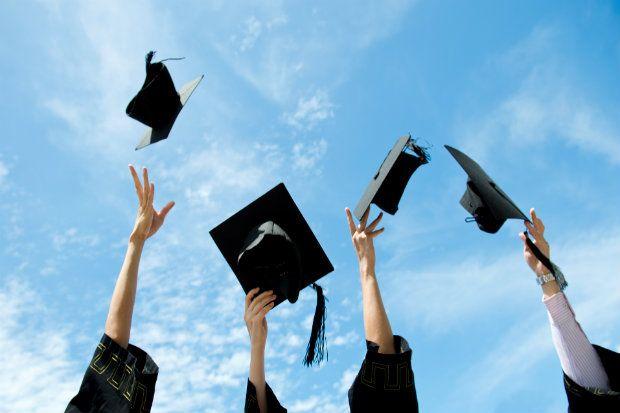 Geslaagd: afbeelding van studenten die hun hoofddeksels in de lucht gooien